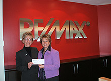 Photo of Lori with Christine Martisavish from RE/MAX Promotions accepting a cheque for Children's Miracle Network