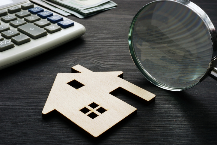 Wooden house with magnifier and calculator