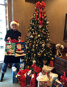 Photo of Lori standing in front of the Christmas Tree with presents in support of Children Of Christmas Past